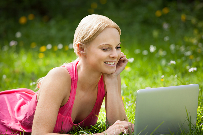 Frau mit Laptop in der Wiese